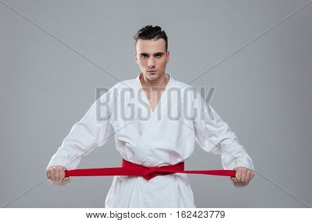 Picture of sportsman dressed in kimono practice in karate while tightening red belt isolated over grey background. Look at camera.