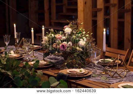 Decoration wedding table before a banquet in a wooden barn. Candles bouquet stemware.