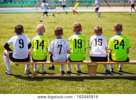Boys Playing Soccer. Young Football Players. Young Soccer Team Sitting on Wooden Bench. Soccer Match For Children. Young Boys Playing Tournament Soccer Match. Youth Soccer Club Footballers