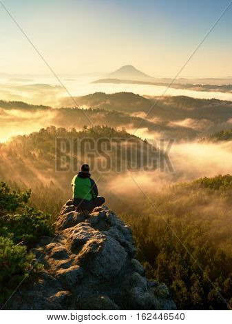 Man Tourist Sit On Exposed Rock. View Point With Heather And Branches