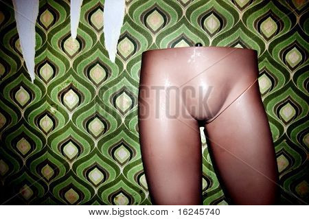 mannequin legs on an old geometric wallpaper background