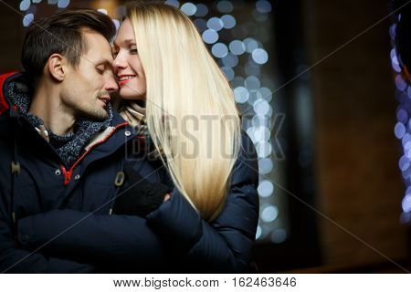 Happy spouses winter in street on background of night lights