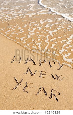 sentence happy new year written in the sand of a beach