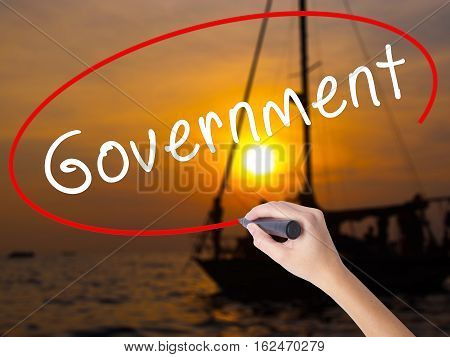 Woman Hand Writing Government With A Marker Over Transparent Board