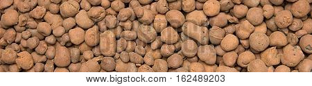 Heat expanded clay pebbles used as a growing media in hydroponics. Background close up of pellets, border design panoramic banner