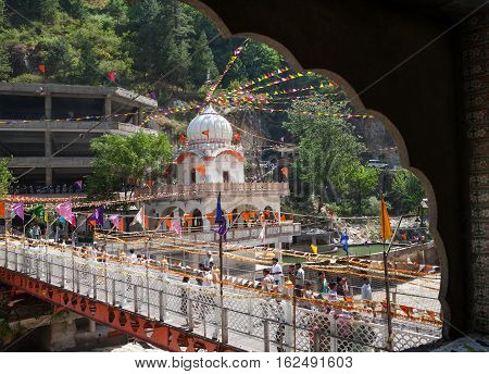 View of the pedestrian bridge and the pool of Gurdwara Sri Guru Nanak Dev Ji. Manikaran, North India
