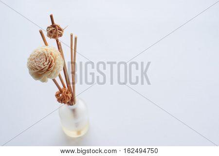 Closeup of air freshener sticks in bottle over white background