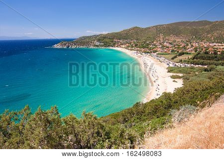 Aerial view on the beach Solanas with white sand hills with green vegetation sea with blue transparent water and village in the province Sinnai. Location Sardinia Italy.