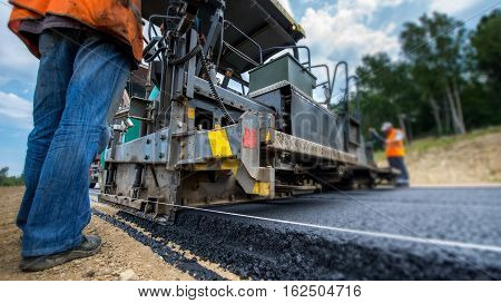 Paving new road with asphalt, road construction