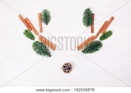 Deer face made of fir branches, cinnamon sticks and pine cone. White wooden rustic background. Winter flat lay style picture.