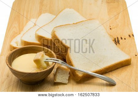 Portion of bread dip in sweetened condensed milk on wooden board