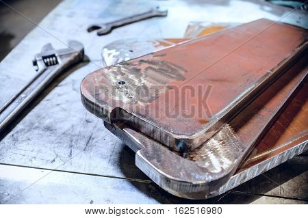 Adjustable and open-end wrenches. Steel metal plate stacked. Abstract industrial background.