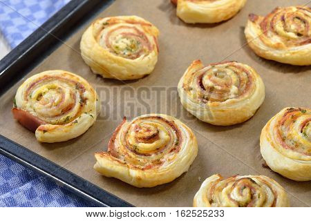 Baked hearty puff pastry rolls with ham, cream cheese, parmesan and herbs on a griddle