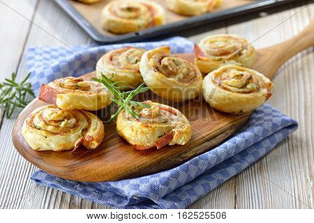 Baked hearty puff pastry rolls with ham, cream cheese, parmesan and herbs