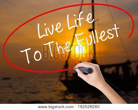 Woman Hand Writing Live Life To The Fullest With A Marker Over Transparent Board