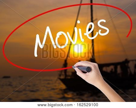 Woman Hand Writing  Movies With A Marker Over Transparent Board