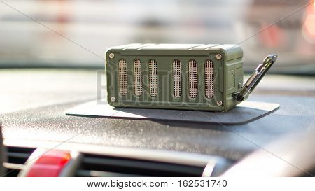 Bluetooth speaker and car entertainment device concept - Green color bluetooth speaker on car console with traffic jam and copy space