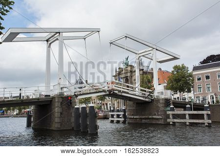 Old white bridge under the cloudy sky in the day in the center of Haarlem in the Netherlands with several buildings as background