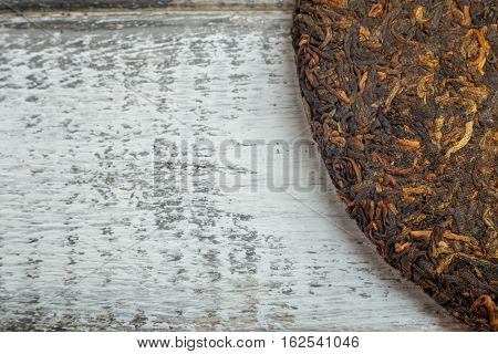 Close up image of old Shu puerh chinese fermented tea on rustic wooden background with copyspace. Top view