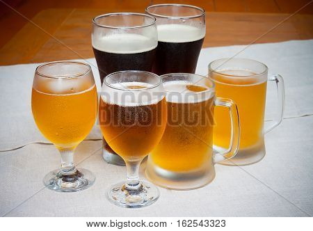 Different kinds of beer in glasses on table
