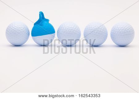White golf balls with funny cap on the white background. Funny golf concept.