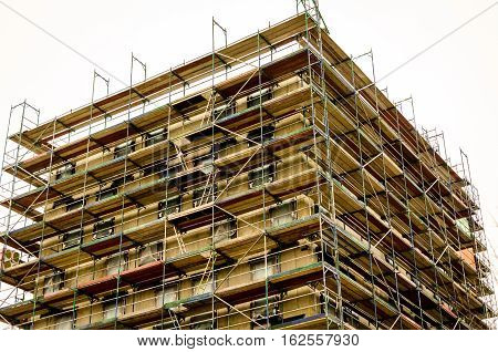 bare brickwork of a city building with scaffold