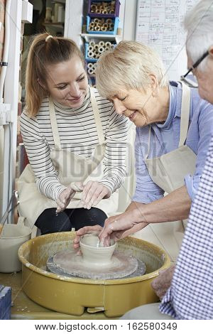 Group Of Seniors With Teacher In Pottery Class