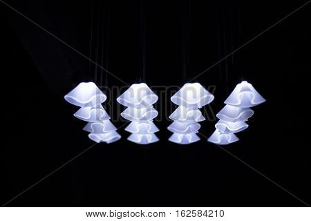 Bright Lamps shine in a black room on dark background