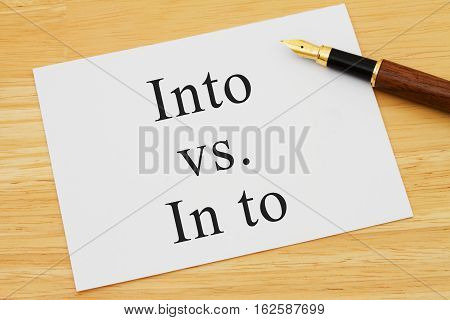 Learning to use proper grammar A white card on a desk with a pen with words Into vs In to