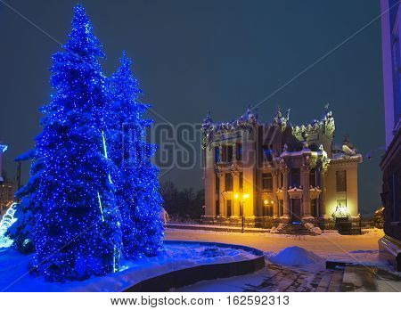 Illuminated House with Chimaeras or Horodecki House (Kiev). Night scene. Illuminated fir-trees in foreground. Building and street are powdered with snow.