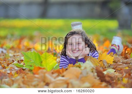 little girl laying on autumn leaves