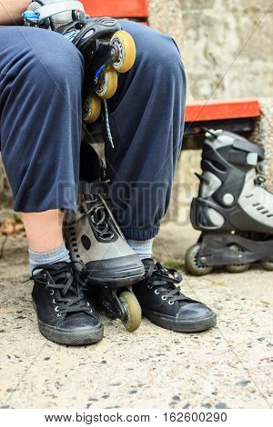 Closeup of man guy putting on roller skates outdoor.