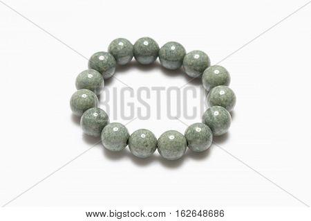 Lucky green stone bracelet on white background.