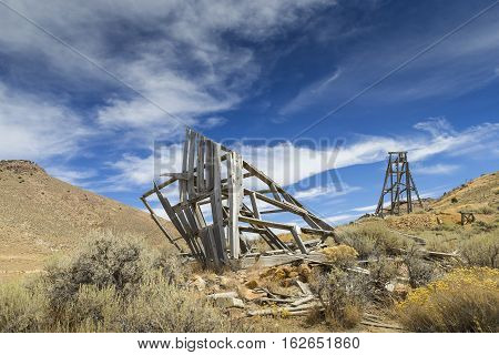Old mining head frame in the Nevada Desert under blue sky with clouds.