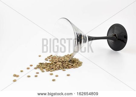 Natural organic dry lentils and glass fell on white background. Conceptual/abstract representation of the end of holidays. The end of the party. Back to the real life. NYE.