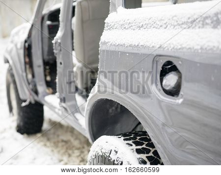 Abandoned partially disassembled car covered with snow focus in the foreground outdoor shot