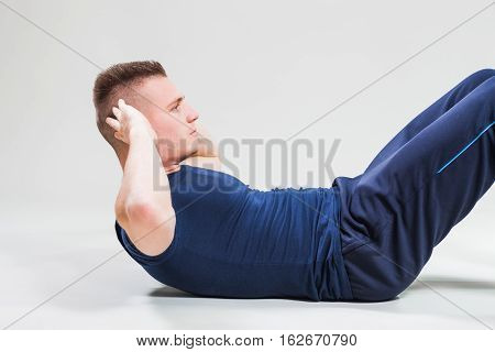Studio shot image of young man who is doing crunches.