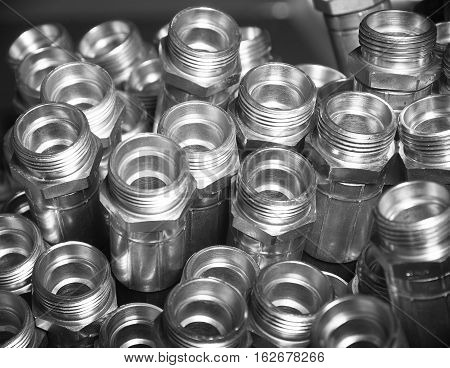 Heap of metal hydraulic fittings, black and white image
