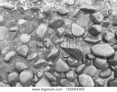 Beach pebbles in the water. Black and white seaside photo background with sea stones. Round rocks in sea water. Coastal texture monochrome image. Beach pebbles surface banner template
