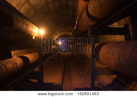 Round underground tunnel of heating duct with rusty tubes