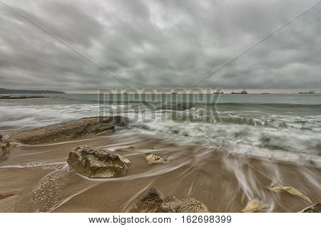 Beauty cloudy long exposure seascape with slow shutter and waves flowing out.