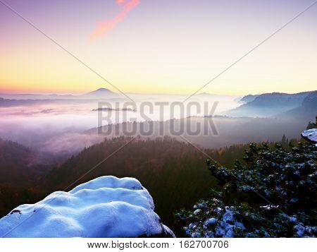 First Powder Snow Cover On Sandstone Rocks Above Valley. Heavy Mist