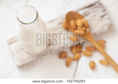 Almond milk in a glass bottle and almond nuts on a stand horizontal