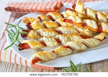 Baked hearty puff pastry sticks with ham and herbs