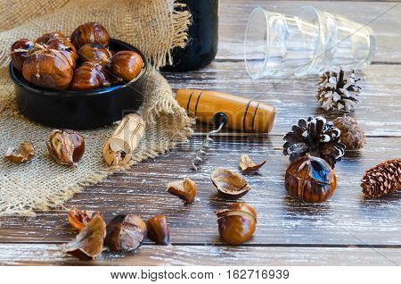 Delicious roasted chestnuts on ceramic bowl and crystal glasses on old wooden table bottle of wine fir cone cork and vintage corkscrew in the background.