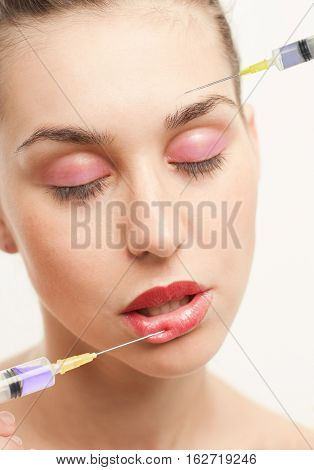 Woman getting two injection or hyaluronic collagenHA injection in lips and at one's head