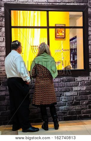 TEL AVIV ISRAEL - DECEMBER 22 2016: Elderly couple at Showcase Judaica store before the holiday of Hanukkah menorahs exposed to different sizes and designs (traditional candelabra)