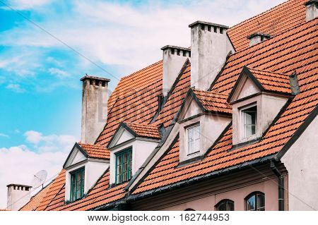 Riga, Latvia. The View Of Mansard Red Tile Roof With Four Gable Fronted Dormer Windows On The Old Building Under Blue Sky.