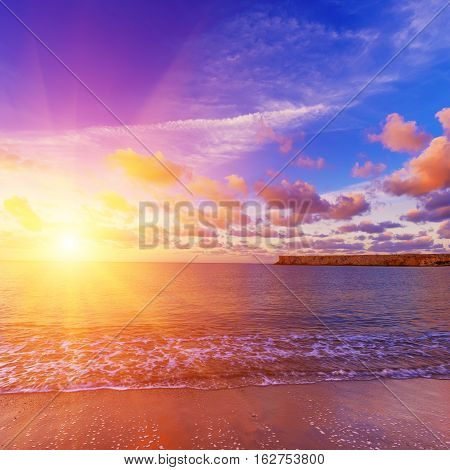 Beautiful colorful sunrise at the sea with dramatic pink clouds over blue sky and soft waves. Beauty world natural outdoors travel background with sun shining