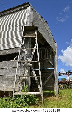 A rickety old wood step ladder leans against acquaint storage shed in a junkyard